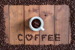 Top view cup of coffee with coffee beans square frame on wooden. Background Stock Image