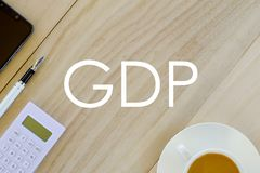 Top view of a cup of coffee,calculator,pen and mobile phone on wooden background written with GDP Gross domestic product or Good. Distribution practice on stock images