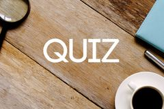 Top view of a cup of coffee,magnifying glass,notebook and pen on wooden background written with QUIZ.  Stock Image
