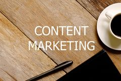 Top view of a cup of coffee,notebook and pen on wooden background written with CONTENT MARKETING stock photos