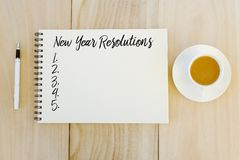 Top view of a cup of coffee,pen and notebook written with New Year Resolutions on wooden background.  royalty free stock photos