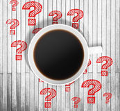 Top view of a cup of coffee and red drawn question marks around it on the wooden table. Royalty Free Stock Photography