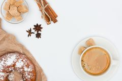 Cup of coffee with saucer and brown sugar, pastry, anise stars and cinnamon sticks tied with rope isolated on white Stock Photos
