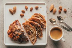 Top view of cup of coffee and sweet pastry with almonds. On plate on light tabletop Stock Photography