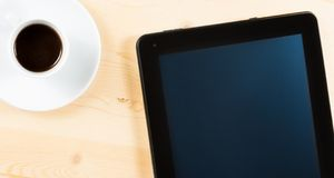 Top of view of cup of coffee and tablet, concept of new technology Stock Photo