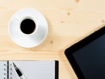 Top of view of cup of coffee and tablet near notes, concept of new technology Royalty Free Stock Photos