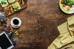 Top view of cup of coffee, tablet, tablecloth and breakfast. On wooden tabletop royalty free stock photos