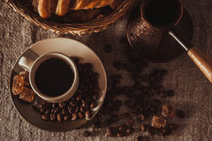 Top view cup of coffee on textile with beans, dark candy sugar, pot, basket and cake Royalty Free Stock Image
