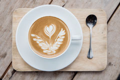 Top view of a cup of coffee on a wooden table. Top view of a cup of coffee, cappuccino on a wooden table Royalty Free Stock Images