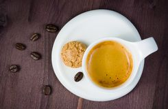 Top of view of cup of espresso coffee and biscuit near coffee beans Royalty Free Stock Photo