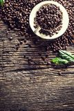 Top of view cup full of coffee beans on rustic oak table royalty free stock image