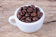Top view cup full of coffee beans on wood surface stock photos