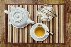 Top view of a cup of green tea, teapot and sugar Stock Photo
