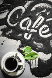 Top view on cup of hot black coffee with green leaves and text word hand written in french `café` in milled coffee texture Stock Photos