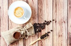 Top view of a cup of hot coffee and coffee beans in a wooden scoop and spilling out from a hessian bag on wooden rustic. Table. Space for text royalty free stock photos
