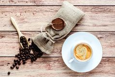 Top view of a cup of hot coffee and coffee beans in a wooden scoop and spilling out from a hessian bag on wooden rustic. Table. Space for text stock image