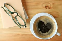Top View of a Cup of hot coffee with heart shape foam on wooden table with some books and glasses. Background Royalty Free Stock Images