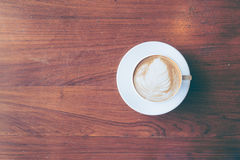 Top view of a cup of hot coffee put on old wooden table backgrou. Nd.Vintage tone with copy space royalty free stock photography