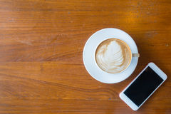 Top view of a cup of hot coffee and smartphone put on old wooden. Table background.Copy space stock photography