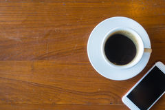 Top view of a cup of hot coffee and smartphone put on old wooden. Table background.Copy space stock photos