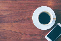 Top view of a cup of hot coffee and smartphone put on old wooden. Table background.Vintage tone with copy space stock photos