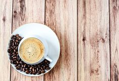 Top view of a cup of hot coffee on wooden rustic table with spilled coffee beans. stock photos