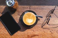 Top view of cup of hot milk coffee with latte art, smartphone, eye glasses and brown sugar on wooden desk in the morning light. Top view cup of hot milk coffee royalty free stock photo