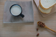 Top view cup of milk with bread and  Almonds for breakfast  on wooden table. Stock Photography
