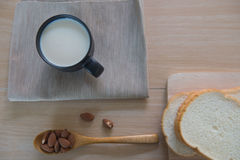 Top view cup of milk with bread and  Almonds for breakfast  on wooden table. Stock Images