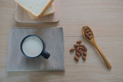 Top view cup of milk with bread and  Almonds for breakfast  on wooden table. Royalty Free Stock Images