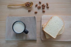 Top view cup of milk with bread and  Almonds for breakfast  on wooden table. Royalty Free Stock Photos