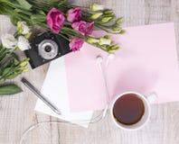 Top view of cup of tea, flowers, vintage camera, earphones, pen Royalty Free Stock Photos