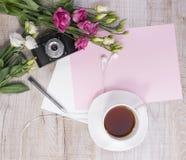Top view of cup of tea, flowers, vintage camera, earphones, pen Stock Images