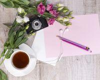 Top view of cup of tea, flowers, vintage camera, earphones, penc Stock Images