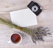 Cup of tea, lavender, vintage camera and sheet of paper on a li Royalty Free Stock Photography