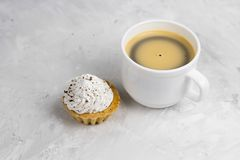 Top view cupcake with cream decorated with chocolate chips and coffee cup. Cupcake with cream decorated with chocolate chips and black coffee cup  concrete Royalty Free Stock Photo