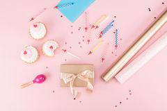 Top view of cupcakes, colorful candles and wrapping paper on pink Royalty Free Stock Images