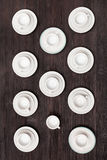 Top view of cups and saucers on dark brown table Royalty Free Stock Images