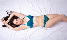 Top view of curly brunette in blue lingerie Stock Photos