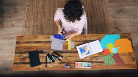 Top view of curly-headed woman making colorful paper collage sitting at table cutting figures with scissors. Design. Top view of slim curly-headed woman making stock footage