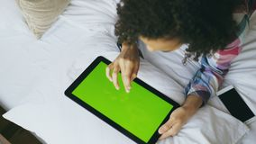 Top view of curly mixed race woman lying in bed at home using electronic tablet with green screen