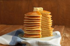 Top view of cut stack of pancake with honey and butter on top. Close up. Cut stack of pancakes with honey and butter on top stands on plate with knife on wooden Stock Image
