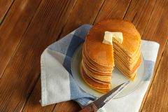 Top view of cut stack of pancake with honey and butter on top. C. Cut stack of pancakes with honey and butter on top stands on plate with knife on wooden table Royalty Free Stock Photos