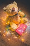 View of a teddy with a red wrapped present, and Christmas decorations on wooden background royalty free stock photos