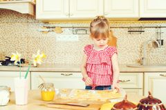 Cute little daughter is cutting cookie dough in different shapes. Daughter helps her mother bake cookies in a kitchen. Royalty Free Stock Images