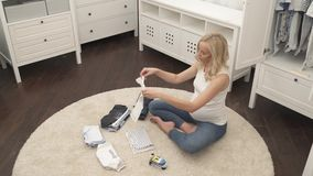A top view of a cute pregnant blonde sitting on the carpet. She folding baby`s T-shirts. A top view of a cute pregnant blonde sitting on the carpet. She is stock footage