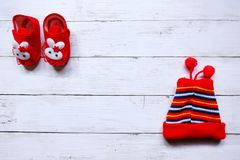 Top view of cute red baby shoe and baby red snow cap on white  wooden background with copy space.  Stock Images
