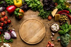 Fresh vegetables and herbs. Top view of cutting board, fresh vegetables and herbs on wooden tabletop Royalty Free Stock Photography