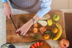 Top view of cutting board with fruit and female hands slicing strawberry for cake decoration Stock Photos