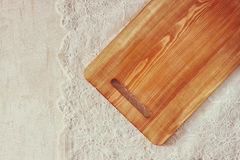 Top view of Cutting board on wooden table over vintage lace table cloth and wooden table. room for text Stock Image